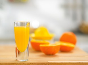 Closeup on glass of fresh orange juice and oranges on table