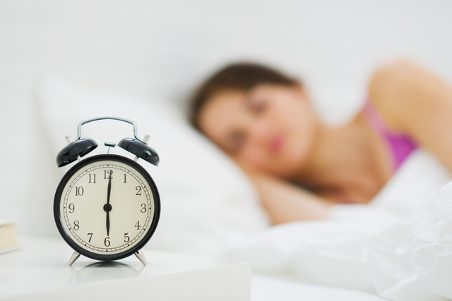 Alarm clock on table and woman sleeping in background