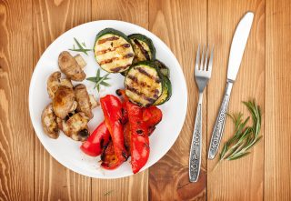 Grilled vegetables and silverware over wooden table background. View from above