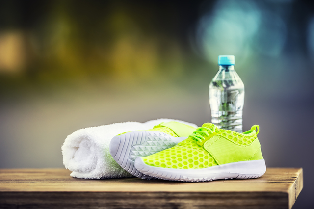 Pair of yellow green sport shoes towel water smart pone and headphones on wooden board. In the background forest or park trail.Accessories for running sport