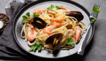 Spaghetti seafood pasta with clams and prawns. White wine glass.