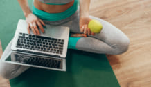 Close up woman in lotus pose with laptop on legs